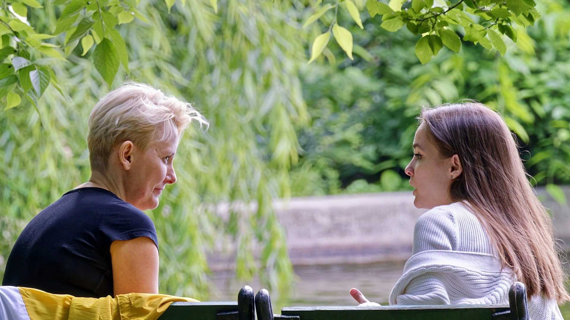 An image of women having a conversation whilst sat on a bench.