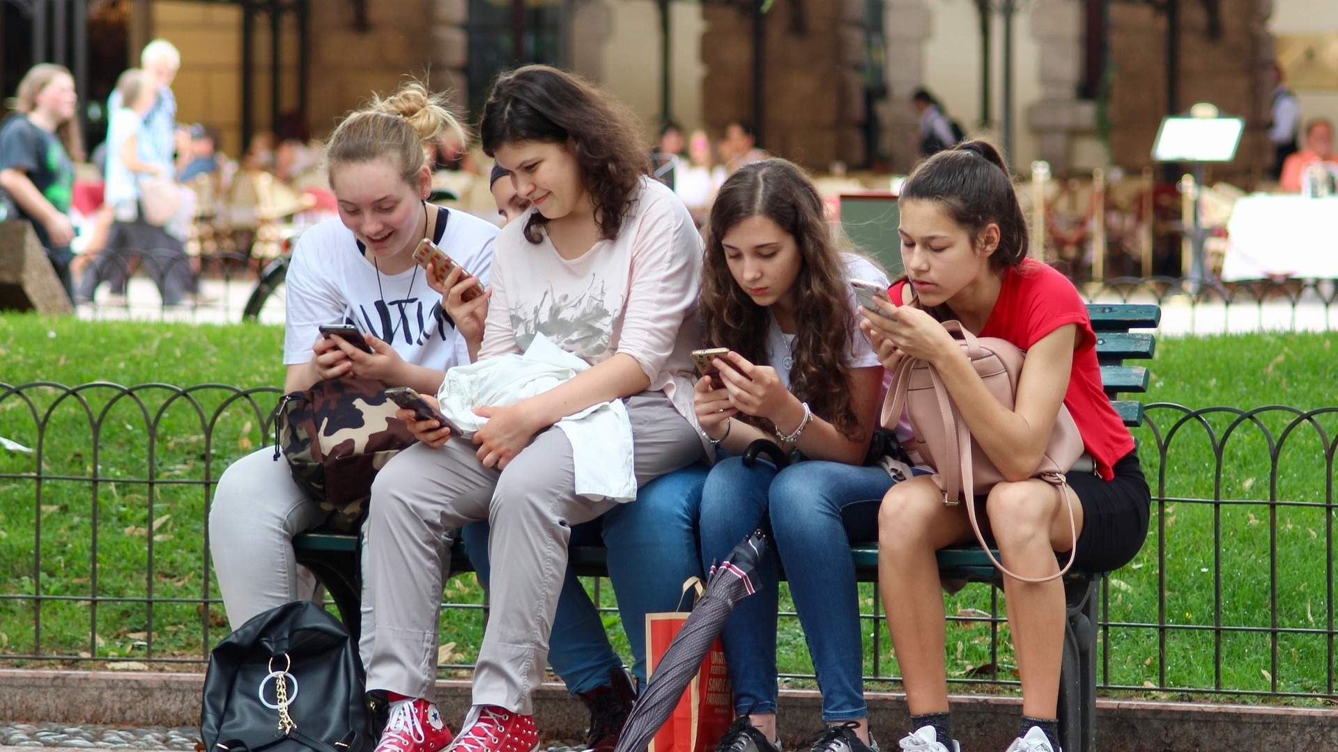 A group of friends sitting on a bench whilst texting.