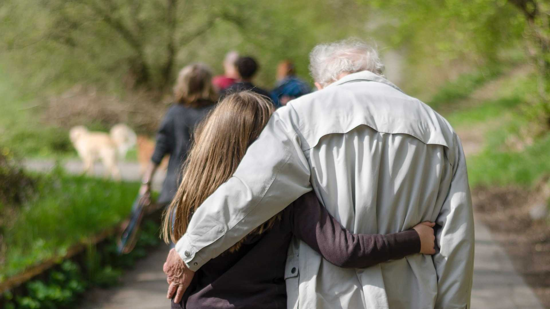 An image of women old man walking alongside a young girl in a park.